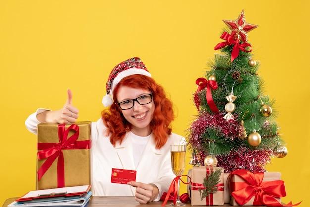 Médica com presente e cartão do banco amarelo