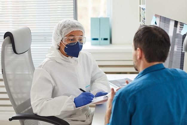 Médica com roupas de proteção fazendo anotações em um documento enquanto ouve o paciente