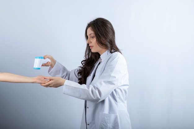 Médica com termômetro, verificando a temperatura de alguém.