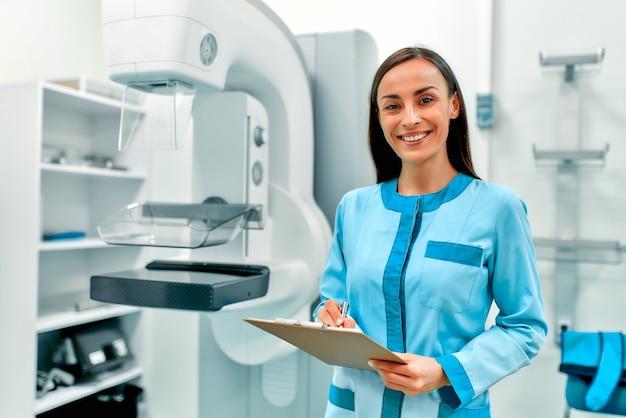Médica com um cartão de paciente em pé perto do aparelho de mamografia