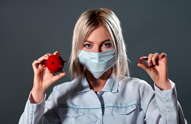 Médica com uma máscara protetora médica segura um modelo 3d de infecção por coronavírus nas mãos e uma cápsula do medicamento é isolada no preto.