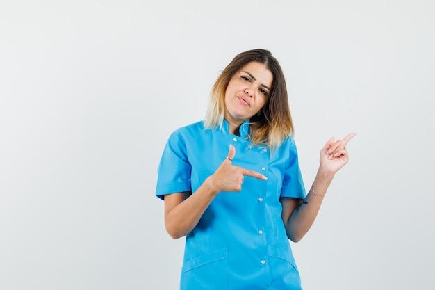 Médica com uniforme azul apontando o dedo para longe e parecendo confiante