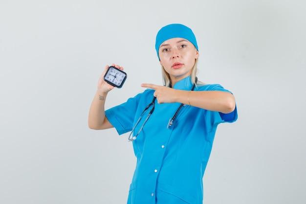 Médica com uniforme azul apontando o dedo para o relógio e olhando séria
