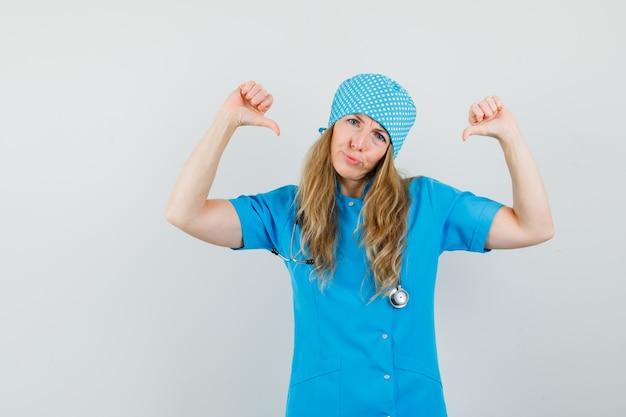 Médica com uniforme azul apontando o polegar para ela