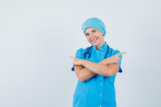 Médica com uniforme azul, apontando para longe e parecendo feliz, vista frontal.