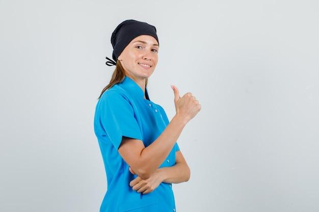 Médica com uniforme azul, chapéu preto aparecendo o polegar e parecendo alegre