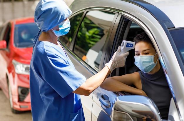 Médica com uniforme azul do hospital e máscara facial em pé perto da fila do drive thru car segurar o equipamento termômetro infravermelho para medir a temperatura da testa da paciente antes de vacinar.