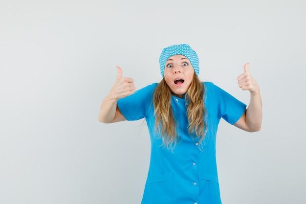 Médica com uniforme azul mostrando dois polegares para cima e parecendo alegre Foto gratuita