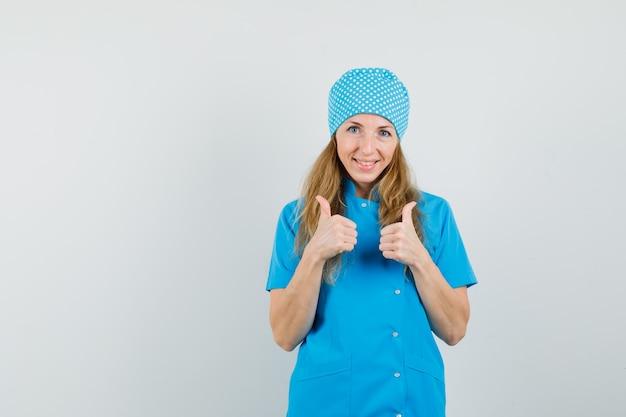 Médica com uniforme azul mostrando dois polegares para cima e parecendo alegre