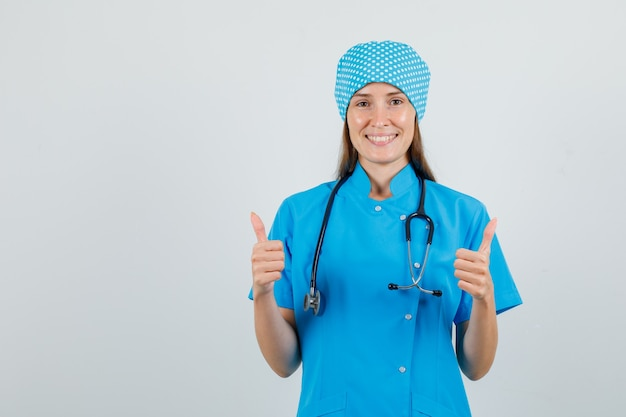 Médica com uniforme azul mostrando os polegares para cima e parecendo alegre