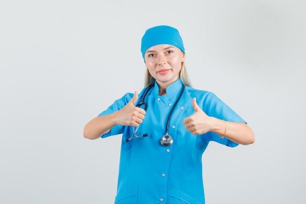 Médica com uniforme azul mostrando os polegares para cima e parecendo satisfeita