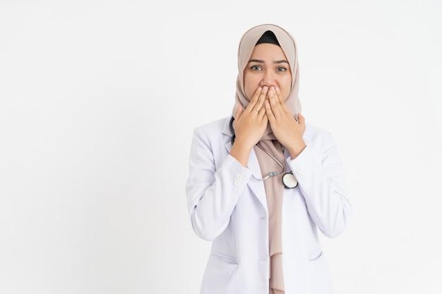Médica com véu usando uniforme de terno branco cobrindo a boca com as duas mãos