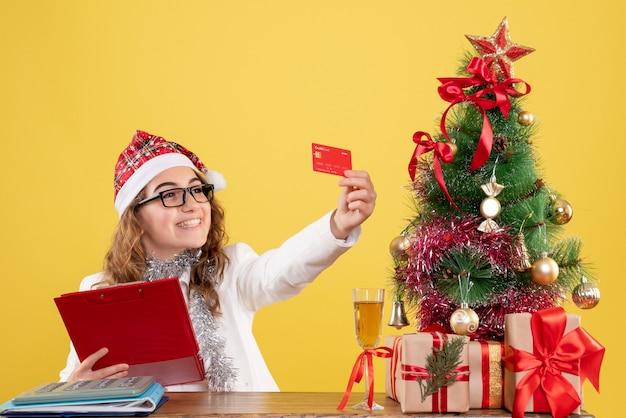Médica com vista frontal segurando a nota do arquivo e o cartão do banco