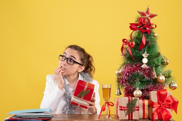 Médica com vista frontal segurando um presente de natal
