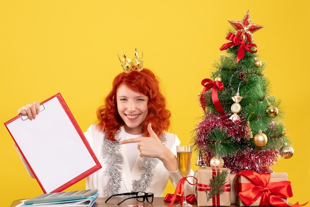 Médica com vista frontal segurando uma nota de arquivo em torno dos presentes de natal e da árvore