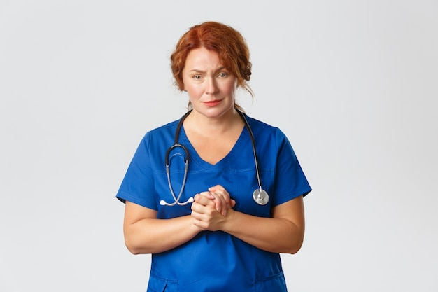 Médica compassiva e preocupada, trabalhadora médica juntam as mãos e imploram que as pessoas fiquem em casa, distância social e usem máscaras