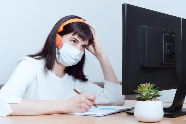 Médica concentrada usando máscara médica e fones de ouvido faz uma videochamada online com um paciente