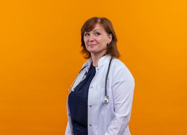 Médica confiante de meia-idade, vestindo túnica médica e estetoscópio em pé na vista de perfil na parede laranja isolada com espaço de cópia