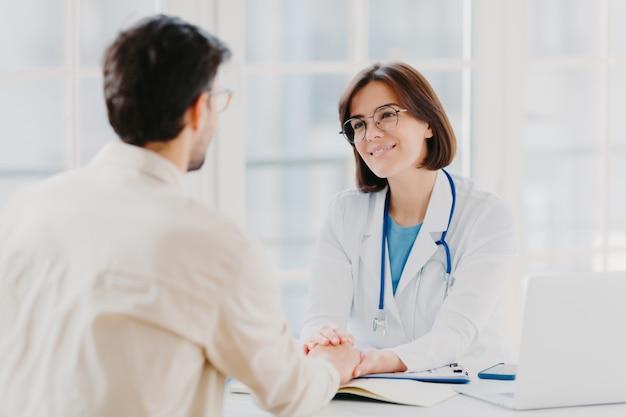 Médica confiante segura as mãos de pacientes doentes e convence que tudo ficará bem
