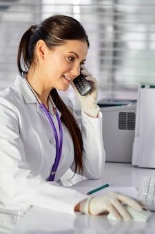 Médica, consultando pacientes por telefone, tendo uma boa conversa, sentada à mesa no local de trabalho, vestindo um terno médico branco e olhando para a tela do computador
