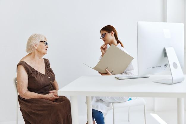 Médica conversando com uma mulher idosa.