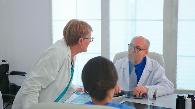 Médica da mulher madura falando sobre o diagnóstico do paciente durante a reunião com sua equipe médica. terapeuta clínico com colegas discutindo sobre doença, especialista, especialista, comunicação.