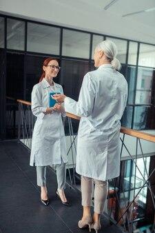 Médica da mulher. vista traseira de uma médica de cabelos grisalhos em um jaleco branco em pé no corredor na frente de seu jovem colega sorridente