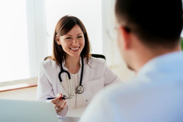 Médica dando uma consulta a um paciente e explicando informações médicas e diagnóstico.