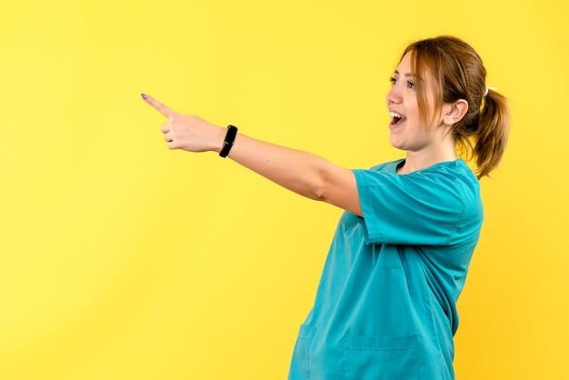 Médica de frente apontando para algo no espaço amarelo