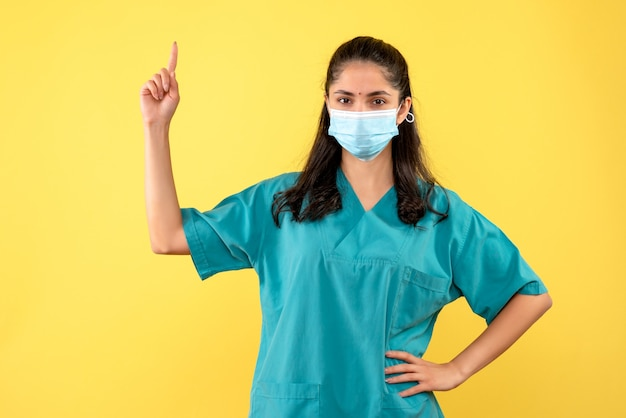Médica de frente apontando para o teto colocando a mão