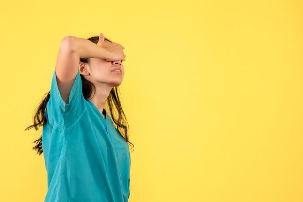Médica de frente cobrindo os olhos com as mãos