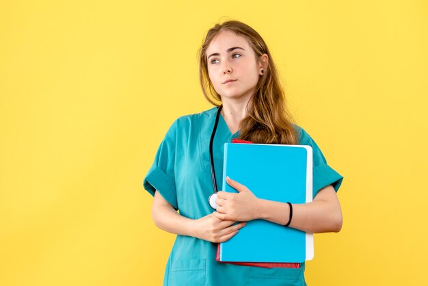 Médica de frente com análises sobre fundo amarelo claro, saúde do hospital médico