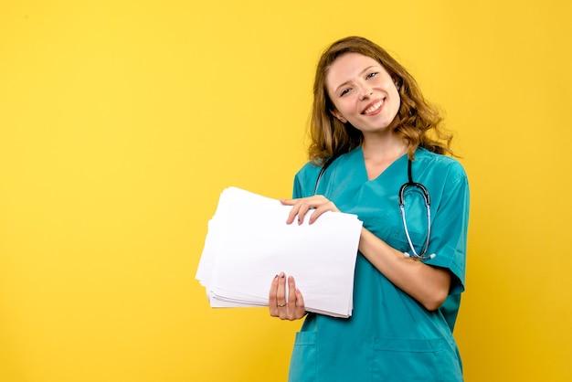 Médica de frente com arquivos no espaço amarelo