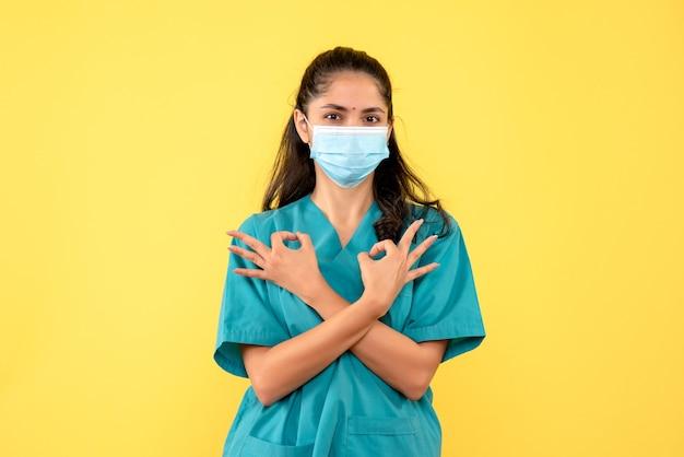 Médica de frente com as mãos cruzadas fazendo sinal de ok