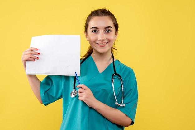Médica de frente com camiseta médica segurando papel de análise, vírus pandêmico saúde covid-19 emoções uniformes