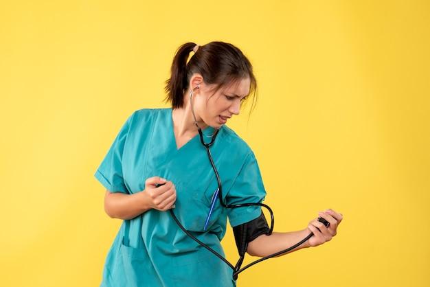 Médica de frente com camiseta médica, verificando a pressão no fundo amarelo