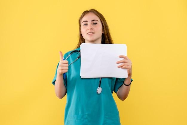 Médica de frente com documentação sobre uma enfermeira de saúde de hospital de fundo amarelo