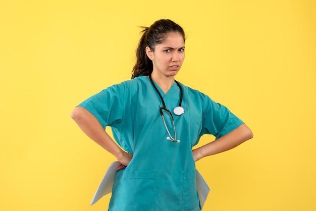 Médica de frente com documentos colocando as mãos