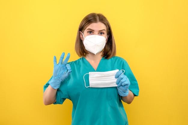 Médica de frente com luvas azuis e máscara no andar amarelo. enfermeira do hospital médico