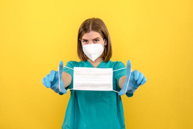 Médica de frente com luvas azuis e máscara no espaço amarelo