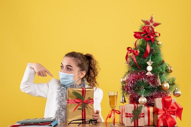 Médica de frente com máscara segurando um presente