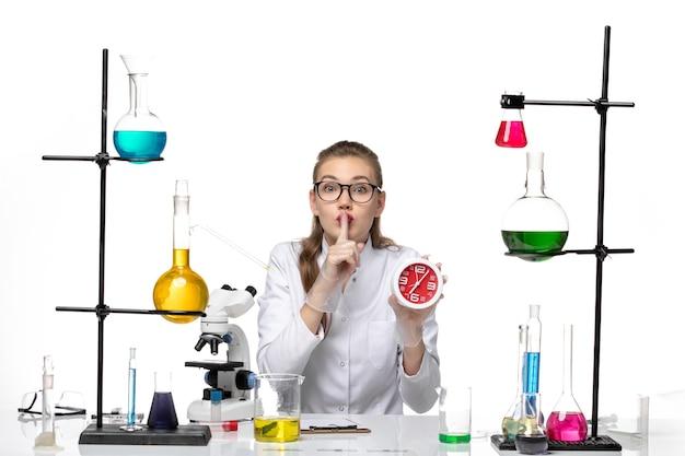 Médica de frente com terno médico branco segurando relógios sobre fundo branco claro vírus química pandêmica covid