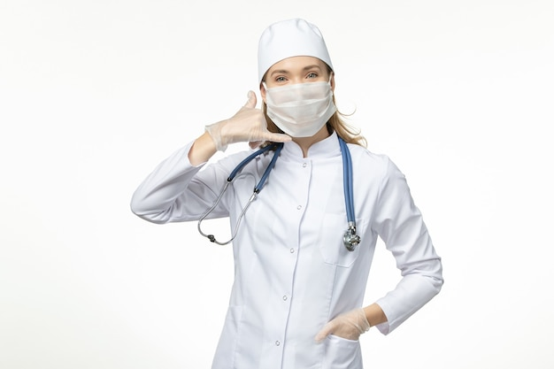 Médica de frente com terno médico usando máscara devido a coronavírus em vírus covidêmico de doença de parede branca clara
