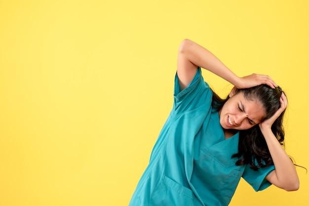 Médica de frente, de uniforme, segurando a cabeça com dor em pé