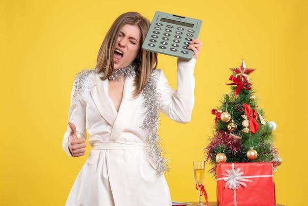 Médica de frente em pé segurando uma calculadora na mesa amarela com uma árvore de natal e caixas de presente