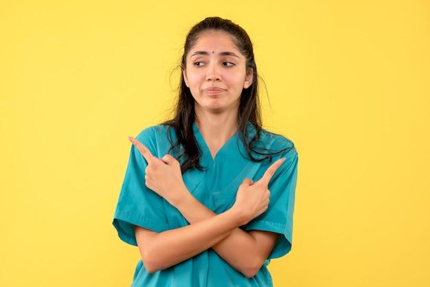 Médica de frente em uniforme, cruzando as mãos em pé
