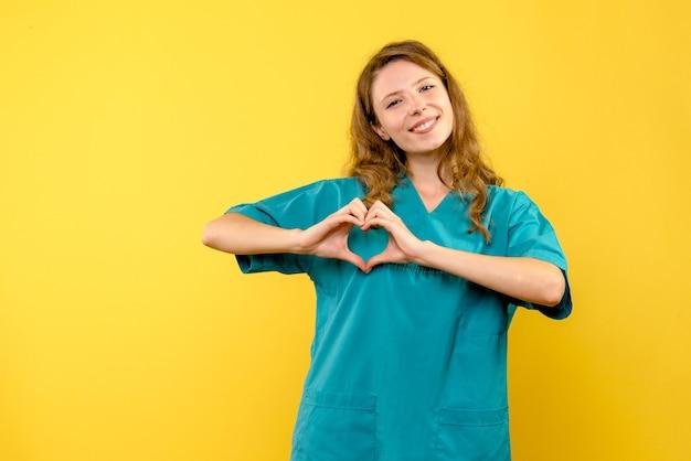 Médica de frente enviando amor no espaço amarelo