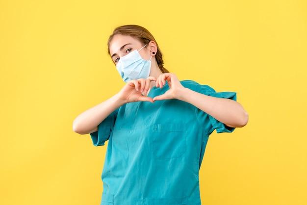 Médica de frente enviando amor sobre vírus de fundo amarelo, pandemia de saúde covid-