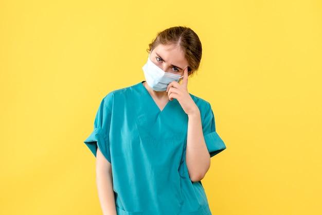 Médica de frente estressada com máscara sobre vírus covid-saúde pandêmico de mesa amarela