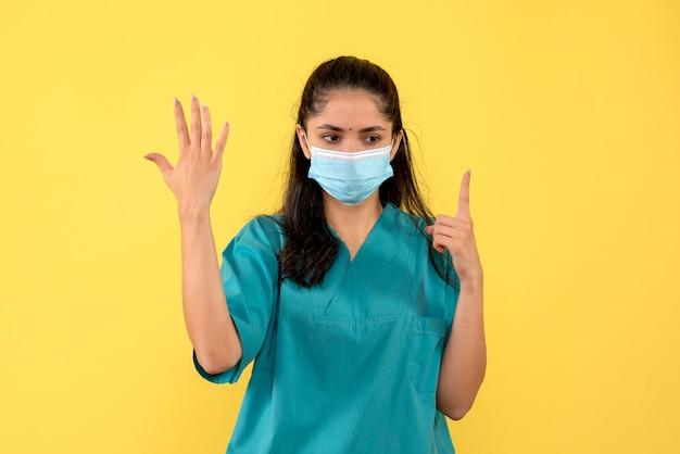 Médica de frente levantando a mão e apontando para o teto